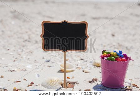 empty black wooden tablet and a pink iron baby bucket with wooden letters on the sand