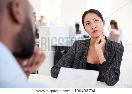 Woman thinking during a job interview in an open plan office