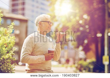 technology, senior people, lifestyle and communication concept - happy old man using voice command recorder or calling on smartphone outdoors