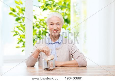 savings, annuity insurance and people concept - smiling senior woman putting money into glass jar at home over window and green natural background