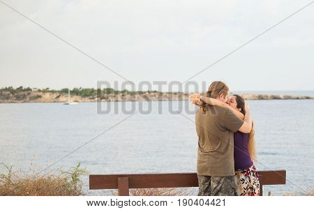 Attractive couple embracing on the beach on a sunny day.