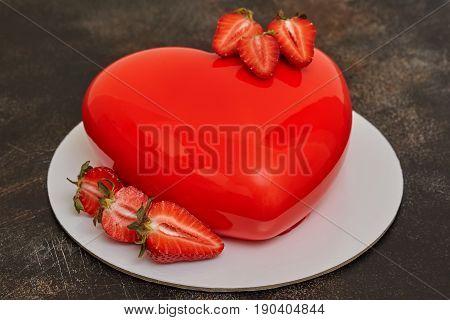 Red strawberry glaze mousse cake heart shape form on dark background closeup