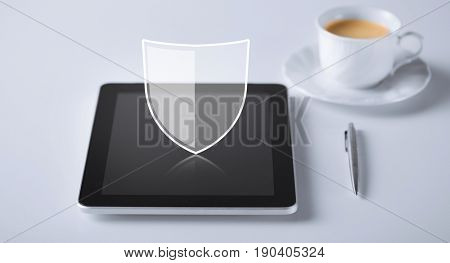 internet security, technology and cyber protection concept - virtual antivirus program shield icon over tablet pc computer with cup of coffee and pen