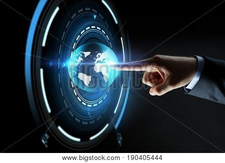 business, people, mass media and technology concept - close up of businessman hand pointing finger to virtual earth projection over black background