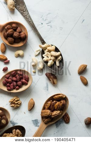 Assorted nuts in spoons, view from above