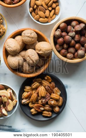 Assorted nuts in wooden bowls on marble table, view from above