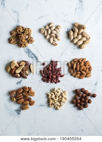 Assorted nuts on white surface, view from above