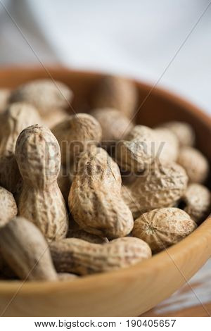 Peanuts in wooden bowl, close-up view