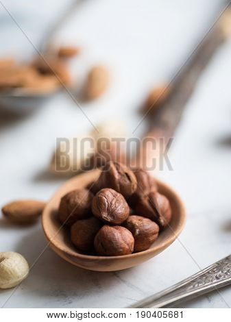 Hazelnuts in wooden spoon, close-up view