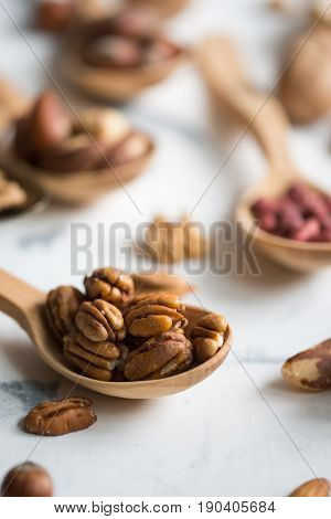 Pecan nuts in wooden spoon on white surface, close-up view