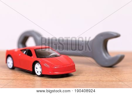 Plastic Toy Wrench Next To Model Car