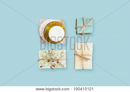 spa, bodycare and natural cosmetics concept - handmade soap bars over blue background