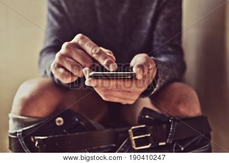closeup of a young caucasian man using his smartphone in the toilet while sitting in the bowl