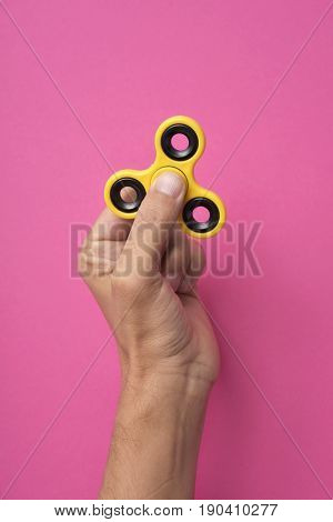closeup of a young caucasian man playing with a yellow fidget spinner against a bright pink background