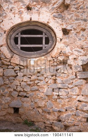 Stone Wall With Round Wooden Window Of A Medieval Fortress.
