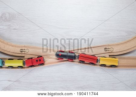 Overhead view of two toy trains at junction on wooden track