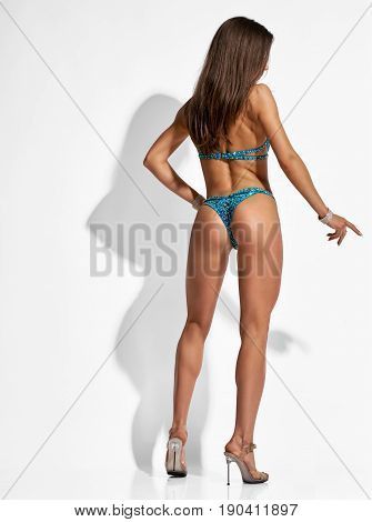 Back view of beautiful muscular bodybuilder woman posing on light grey background with shadow