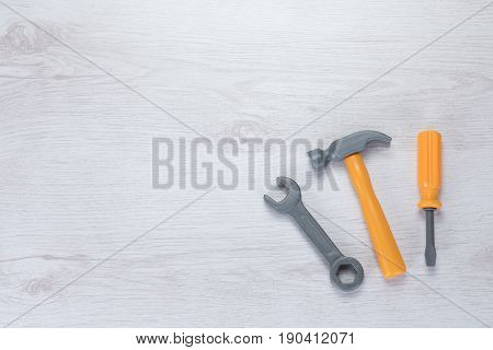 Three Small Hand Tools On White Textured Wood