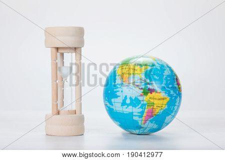 Wooden Egg Timer Alongside A World Globe
