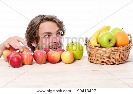 Man Stealing Apple From Wooden Table Near Fruit Basket