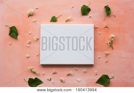 White primed canvas on pink wooden board with flowers and leaves. Mock up poster. Top view.