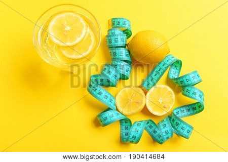 Lemon halves and slices in glass of water and turquoise measuring tape twisting around them isolated on yellow background. Top view