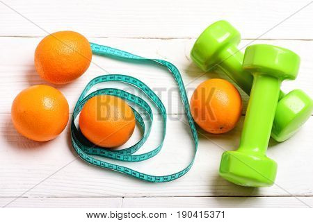 Oranges in turquoise flexible ruler circles and plastic green lightweight dumbbells on white wooden background top view. Concept of sports healthy food and fit shape