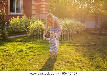 beautiful mother is walking on with her little baby boy son with first steps.