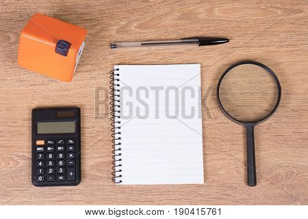House Model With Calculator And Magnifying Glass