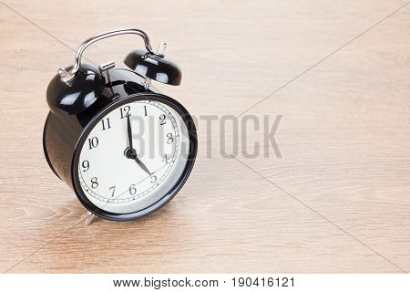 Black Clock Standing Alone On Wooden Background