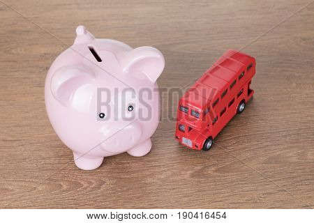 Small Red Toy Bus Next To Pink Piggy Bank