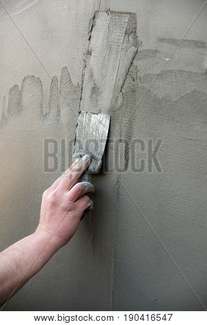 Repairing and finishing work. hand with metallic spatula plastering layer or coat of plaster stucco on cement wall surface texture on grey background. Working tool. Construction and renovation