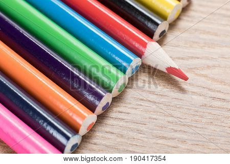 Line Of Colorful Pencil Crayons On Wood