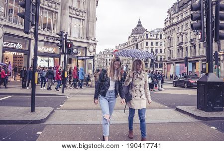 London, UK - March 19, 2017: London leaving the Oxford Circus station in London. Two women cross the street at Oxford Street traffic lights on a cloudy day in March