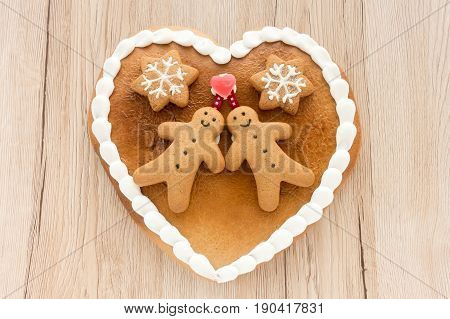 Close up of a cute Gingerbread heart decorated with Gingerbread Men Gingerbread Stars and a Christmas Tree Cookie on light brown wooden background.