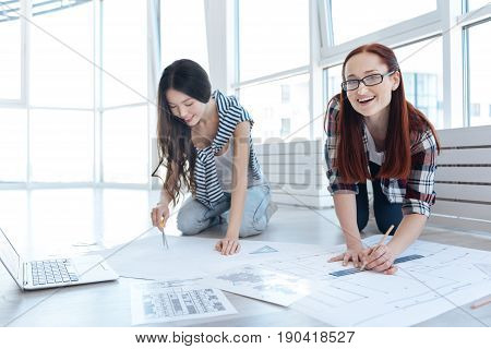 Interesting experience. Joyful young female engineers sitting on the floor and doing drawings while working a project together
