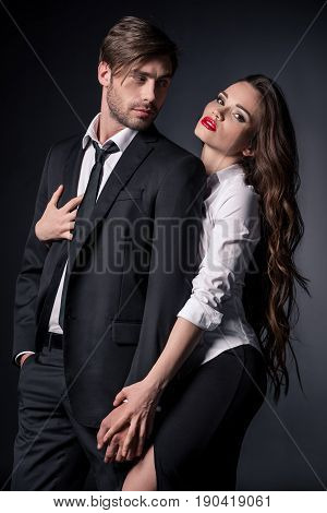 Young Sexy Woman Hugging Elegant Man In Suit Isolated On Black