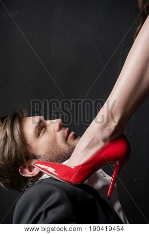 close up of girl stepping on young handsome man with red stiletto