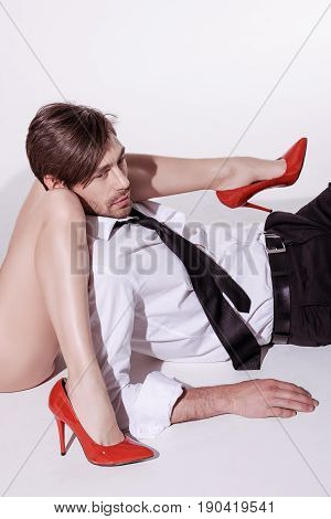 cropped shot of woman in red stilettos lying with young elegant man