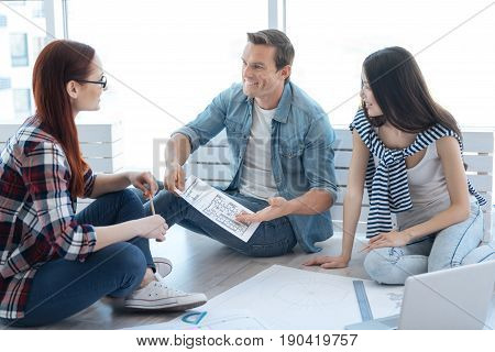 Discussion with colleagues. Handsome cheerful positive man holding a drawing and discussing it with his colleagues while suggesting his ideas