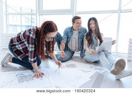 Plan of the building construction. Hard working serious female architect holding a pair of compasses and working on a drawing while developing a building design