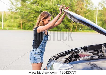 Broken car, accident and people concept - Woman open the car hood and broken automobile on the side
