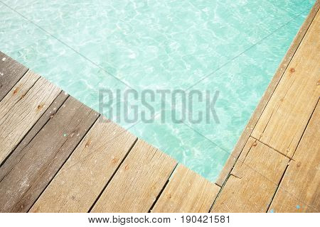 Close up wooden jetty with crystal clear and turquoise sea water of the tropical sea . Top angle view .Rawa island Malaysia .