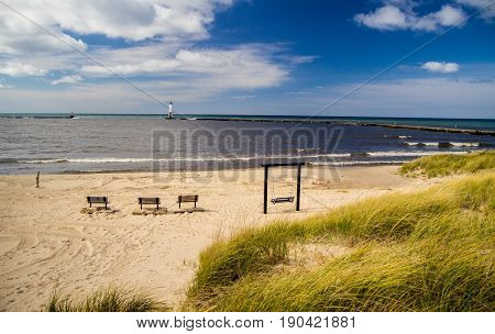 Lake Michigan Beach Background. Wide sandy beach along the coast of Lake Michigan with park bench on the beach and lighthouse in the background. Frankfort, Michigan,