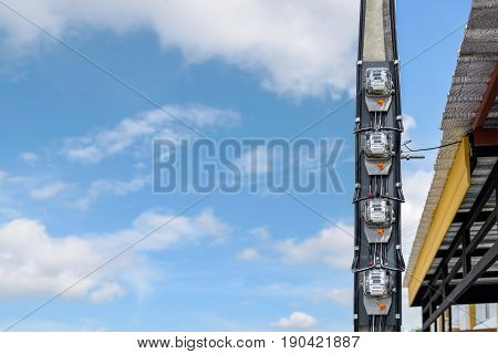Closeup group of electric meters on electric poles with the blue sky background.