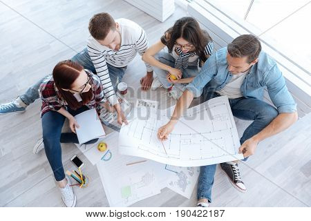 Building scheme. Top view of hard working pleasant architects looking at the blueprint and discussing it while developing the design of the building