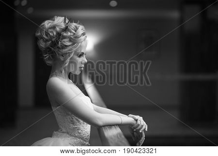 A beautiful bride with blond hair gathered in a voluminous hairdo with fresh flowers in a white lace wedding dress puts her hands on the railing and looks thoughtfully into the distanceblack and white frame