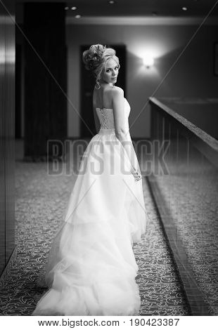 A happy bride with a voluminous hairdo with fresh flowers with bright make-up in a white lace dress with a corset and a long train looks back and flirts a flirtatious smile black and white frame