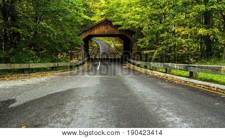Country Road. One lane road on scenic Lakeshore Drive in the northern Michigan forest with a wooden covered bridge. Sleeping Bear Dunes National Lakeshore. Empire, Michigan.