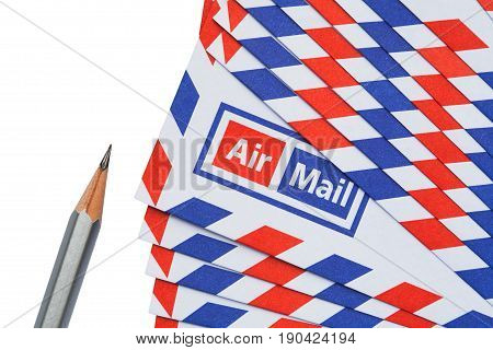 Airmail letter and pencil on white background